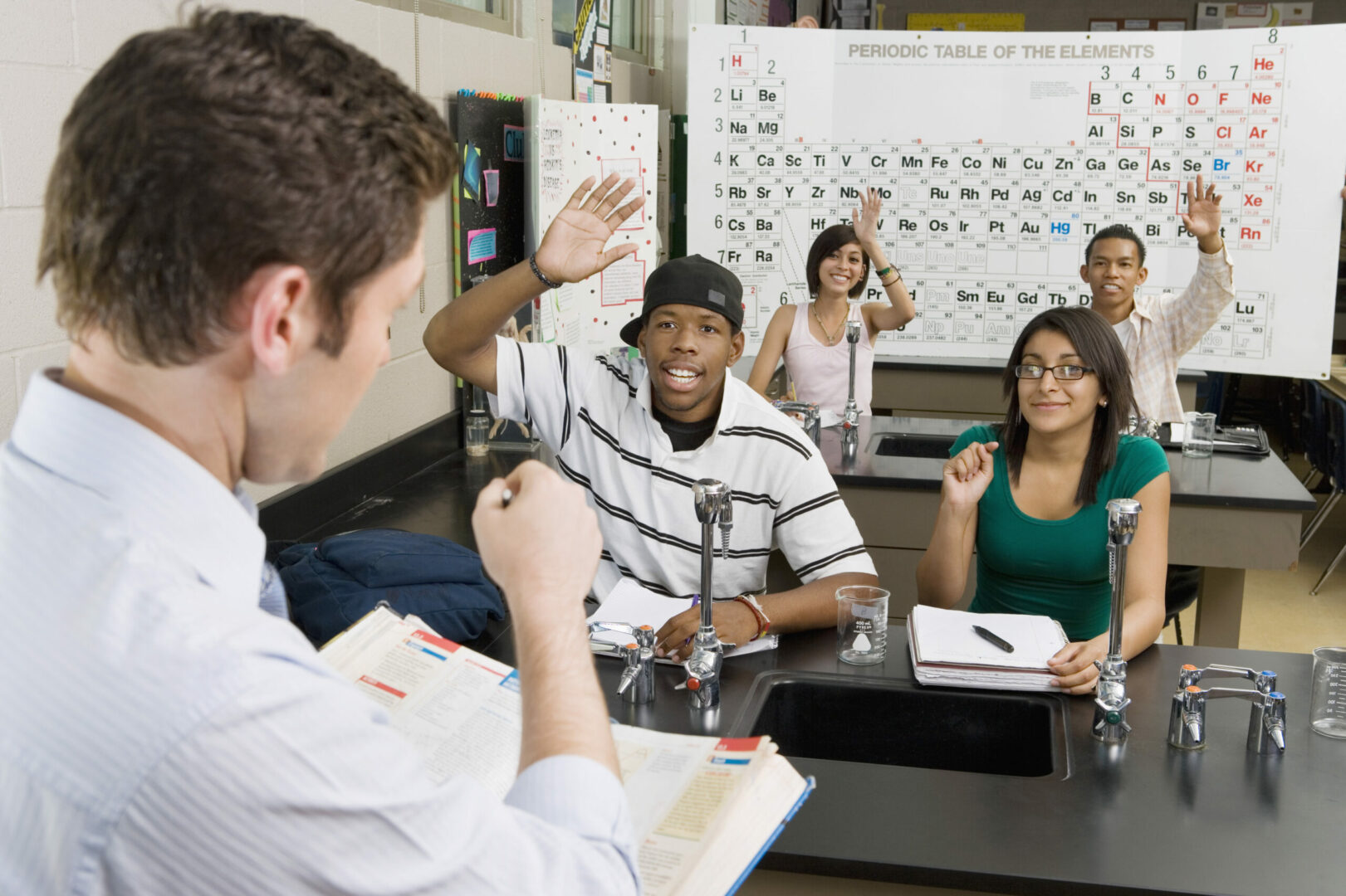 Professor asking question while student raising hand in classroom